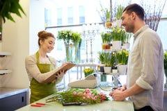 Bloemistvrouw en man die orde maken bij bloemwinkel Stock Afbeelding