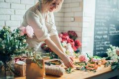 Bloemistwerkplaats: vrouw die een boeket met bloemen schikken royalty-vrije stock foto