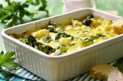 Bloemkool en broccoli in roomsaus die wordt gebakken Stock Foto's