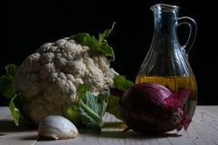Bloemkool, knoflook, ui en olijfolie op een houten lijst Stock Afbeelding