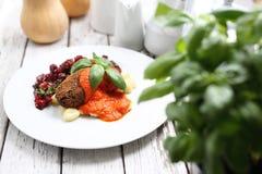 Bloemkoolkoteletten met geroosterde pepersaus worden gediend op bollen op gnocchi, geroosterde bietensalade die stock fotografie