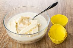 Bloemmengsel met boter, melk voor muffins, lepel in kom, siliconevormen op houten lijst royalty-vrije stock fotografie