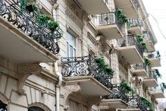 Bloemrijk balkon in een stadsstraat Bloempotten en huisinstallaties op het balkon Klassiek stijlbalkon met bloemen royalty-vrije stock afbeelding