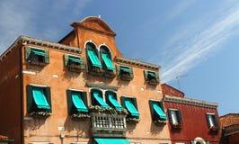 Bloemrijk balkon in Venetiaanse stijl met Vensters en het groene afbaarden royalty-vrije stock foto's