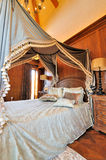 Bloemrijk gordijn van bed in klassieke slaapkamer stock foto