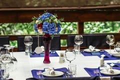 Bloemstuk op huwelijkslijst Bloemensamenstellingen met verse rozen en blauwe bloemen Stock Fotografie