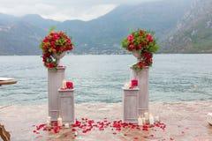 Bloemstuk in steenkom met rode rozen Stock Afbeeldingen
