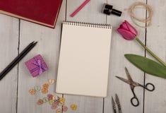 Bloemtulp, giftvakje, notastootkussen, boek, schaar, nagellak en knopen Royalty-vrije Stock Afbeeldingen