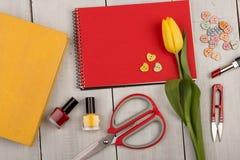 Bloemtulp, leeg rood notastootkussen, geel boek, schaar, nagellak en knopen in de vorm van harten Royalty-vrije Stock Fotografie