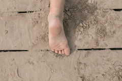 Bloßer Fuß des Kleinkindes auf hölzerner Plattform am Strand Stockbild