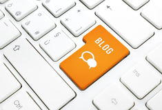 Blog business concept, text and icon. Orange button or key on white keyboard Royalty Free Stock Image