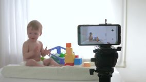 Blog about child development, cute kid boy in unfocused play with educational toys while video recording on mobile phone. For subscribers in social networks in stock video footage