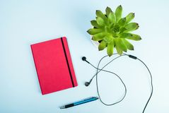 Blog concept photo. Green plant, red notebook, pen and headphones on blue background. Green plant, red notebook, pen and headphones on blue background. Blog royalty free stock images