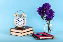 Blog concept photo. Green plant, red notebook, pen and headphones on blue background. Retro clock on book, pen on notebook and purple flower in vase on blue stock photo