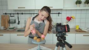 Blog culinario: la mujer joven adorna un capcake con una crema metrajes