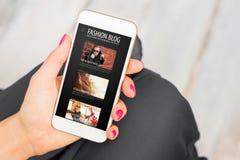 Blog de la moda de la lectura de la mujer en el teléfono móvil imagen de archivo libre de regalías