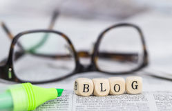 Blog. Formed by wooden letters, on top of newspapers with glasses and pen Royalty Free Stock Photo