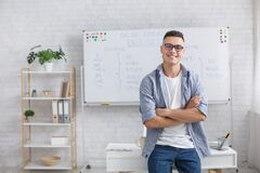 Blog, hobby and remote work from home. Smiling man in glasses with crossed arms makes video for students in living room