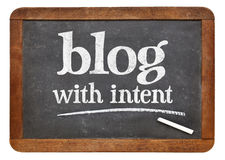 Blog with intent advice or reminder. Blog with intent - blogging advice on a vintage slate blackboard stock images