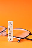 Blog lettering with glasses. Lettering blog and glasses on orange background Royalty Free Stock Photo
