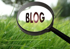 Blog. Magnifying glass with the word blog on grass background. Selective focus Stock Photos
