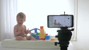 Blog o rozwój dziecka, śliczna dzieciak chłopiec w unfocused sztuce z edukacyjnymi zabawkami podczas gdy nagrywanie wideo na tele zdjęcie wideo