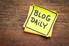 Blog daily reminder note. Blog daily reminder - handwriting on a sticky note against rustic wood stock photography