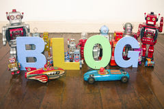 Blog robots. The word   BLOG on wooden floor with reto robots Royalty Free Stock Photography