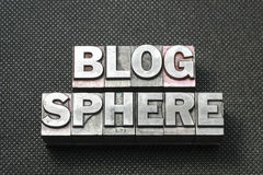 Blog sphere bm. Blog sphere phrase made from metallic letterpress blocks on black perforated surface Royalty Free Stock Images