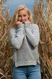 Blog style fashion photo of cute blond woman on corn field in late autumn stock photos