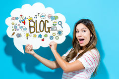 Blog text with young woman holding a speech bubble. On a blue background Royalty Free Stock Images