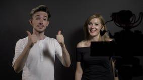 Blog video atractivo joven de la grabación del hombre y de la mujer sobre las últimas tendencias en medios sociales en un estudio almacen de metraje de vídeo