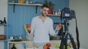 Blog video de la grabación alegre hermosa del hombre sobre la comida sana vegetariana en cámara del dslr en cocina en casa imágenes de archivo libres de regalías