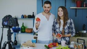 Blog video de la grabación atractiva alegre de los pares sobre la comida sana vegetariana en cámara del dslr en la cocina en casa fotos de archivo