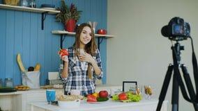 Blog video de la grabación atractiva alegre de la mujer sobre la comida sana vegetariana en cámara del dslr en cocina en casa imagen de archivo libre de regalías
