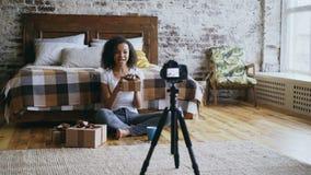 Blog video de la raza mixta de la grabación alegre joven de la muchacha sobre la caja de regalo de la Navidad del embalaje en cas almacen de metraje de vídeo