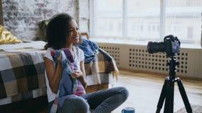 Blog video de la raza mixta de la grabación alegre de la mujer sobre su guardarropa para el viaje con la cámara del dslr en casa Foto de archivo libre de regalías