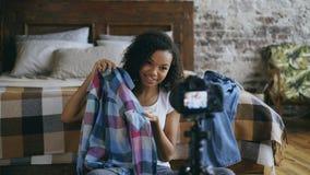 Blog video de la raza mixta de la grabación alegre de la mujer sobre su guardarropa para el viaje con la cámara del dslr en casa Imagenes de archivo
