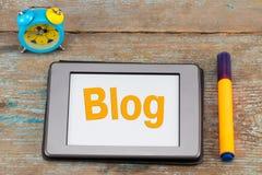 Blogaufschrift auf Tablettenschirm Wecker mit Tablette an Stockbild