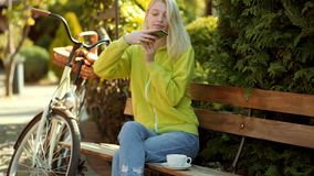 Bloger with coffee. Happy young woman in park on sunny autumn day. Concept about blog morning coffee. stock footage
