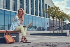 Blogger élégant de mode à l'aide de l'ordinateur portable pour le travail tout en se reposant dehors sur un banc contre un gratte Photos libres de droits