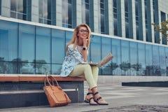 Blogger élégant de mode à l'aide de l'ordinateur portable pour le travail tout en se reposant dehors sur un banc contre un gratte Photos stock