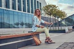 Blogger élégant de mode à l'aide de l'ordinateur portable pour le travail tout en se reposant dehors sur un banc contre un gratte Photographie stock