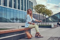 Blogger élégant de mode à l'aide de l'ordinateur portable pour le travail tout en se reposant dehors sur un banc contre un gratte Image stock