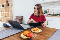 Blogger Учить студента онлайн Женщина сидя на таблице и принимая примечания в тетради Стоковое Изображение RF