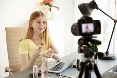 Blogger adolescente con diversos cosméticos que registran el vídeo en la tabla Fotos de archivo libres de regalías