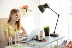 Blogger adolescente con el ordenador portátil y diversos cosméticos en la tabla Foto de archivo