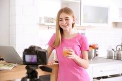 Blogger adolescente con el vidrio de vídeo de la grabación del jugo en la tabla Fotografía de archivo libre de regalías