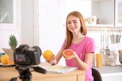 Blogger adolescente con las frutas que registran el vídeo en la tabla Imagenes de archivo