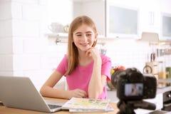 Blogger adolescente con vídeo de la grabación del ordenador portátil en la tabla Imágenes de archivo libres de regalías